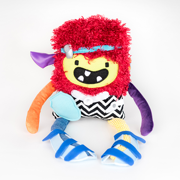 Plush monster from Weesie Pals. Made from a variety of colours and textures of fabric. The monster is also rocking a baha, trach tube, ostomy pouch, g-tube and leg splints.