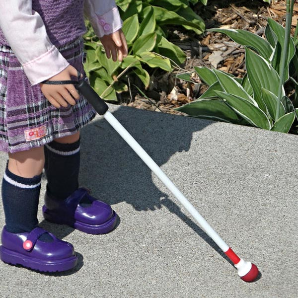 Image shows the legs of a doll walking with a white cane in hand. The white cane has a black handle and red ball.