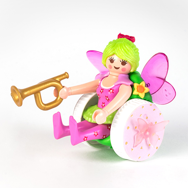 #ToyLikeMe makeover showing Playmobil fairy dressed in pink using a pink, green and white wheelchair with wings. The fairy is holding a gold bugle.