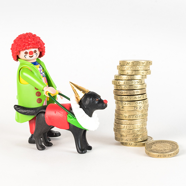 #ToyLikeMe makeover showing Playmobil clown figure with black lab guide dog also dressed in clown clothes. They are stood next to a stack of pound coins.