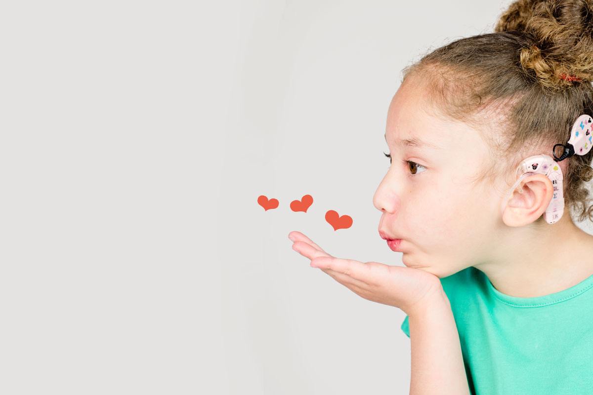 Image shows girl with cochlear implant blowing a kiss. There are hearts around her hand.