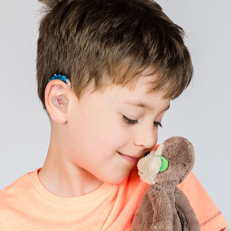 Boy with hearing aid holding a plush monkey, also with a hearing aid.