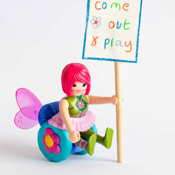 Image shows a #ToyLikeMe makeover of a Playmobil fairy figure. The fairy is sitting in a wheelchair made of modelling clay with a flower on the wheel and wings on the back. The fairy is holding a placard which reads 'come out and play'.