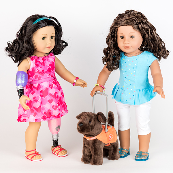 Two American Girl dolls stood next to one another. One has a prosthetic hand and arm, the other has a guide dog.