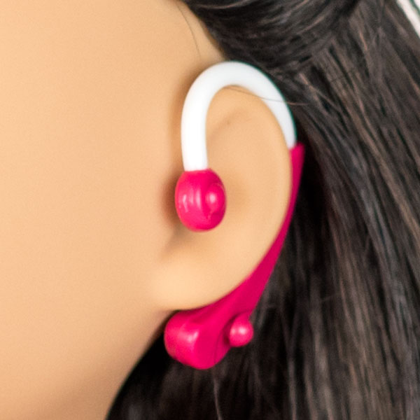 Close up of American Girl hot pink hearing aid on doll