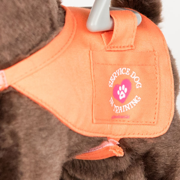 Close up of American Girl toy guide dog harness. Stitching on the harness reads