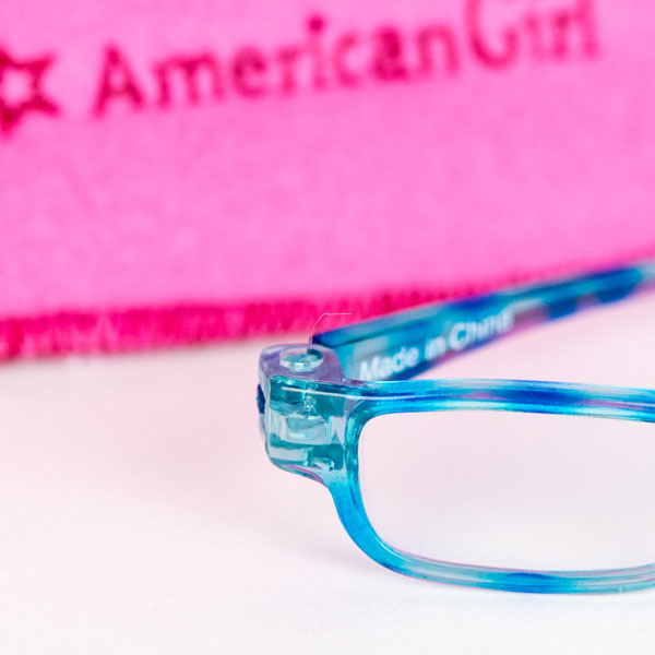Close up of American Girls glasses in blue and pink glasses case in background.