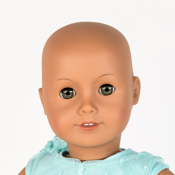 Close up of American Girl doll with no hair, blue eyes and blue lace dress.