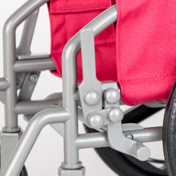 Close up of pink American Girl wheelchair showing break mechanism.