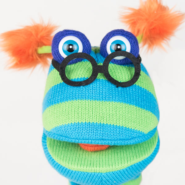 Close up of blue and green striped woolen hand puppet with black glasses and orange fluffy ears.