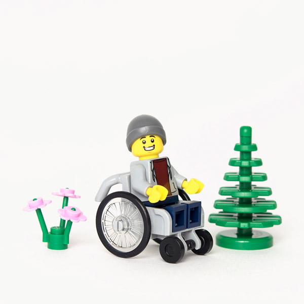 Lego mini-figure in grey hoodie and beaning hat using a grey wheelchair, sat next to Lego tree and flowers.
