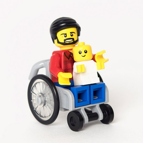 Lego dad mini-figure with red shirt and beard using a grey Lego wheelchair. Mini-figure baby is sat on his knew.