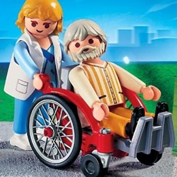 Image shows Playmobil wheelchair set featuring a red wheelchair. The man using the chair is an older man with grey hair and beard. There is a younger woman pushing the chair behind him.