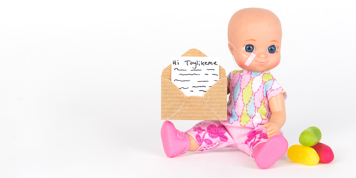 #ToyLikeMe makeover image showing baby girl toy with nasal feeding tube. The doll holding a little envelope.