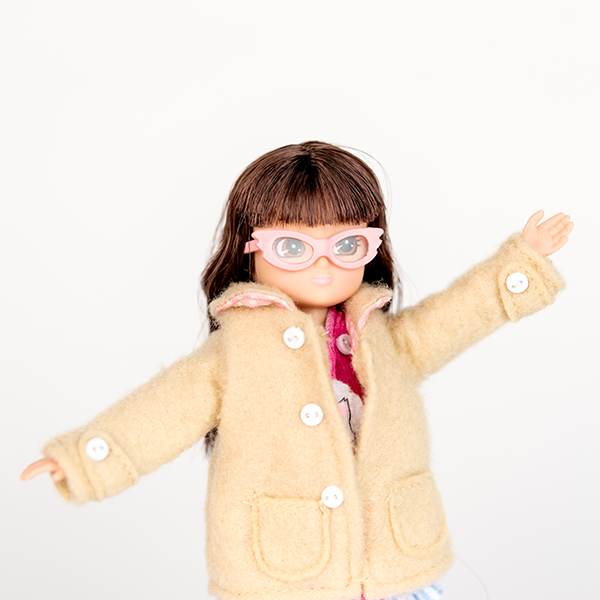 Mid shot of Lottie doll. Doll has brown hair, pale pink glasses and beige coat.