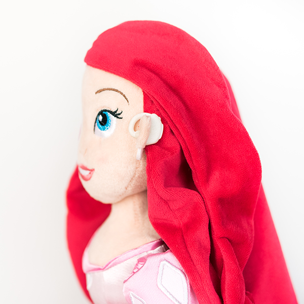 Plush Disney Arial doll with white hearing aid.