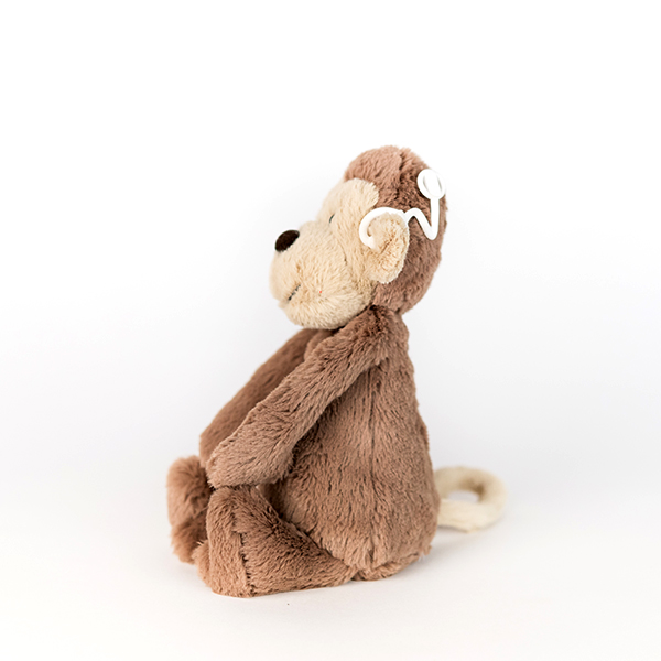 Brown plush monkey with white 3D printed cochlear implant.
