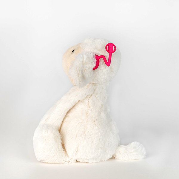White plush monkey with hot pink 3D printed hearing aid.