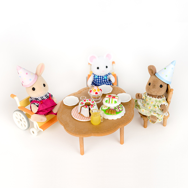 Image shows three Sylvanian figures having a tea party around a table. They are wearing party hats. Two figures are using wheelchairs.