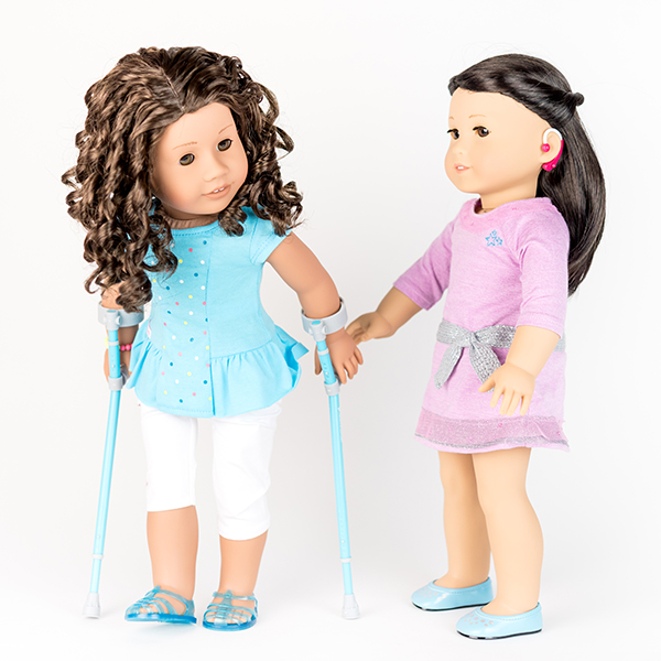 Two American Girl dolls. One with a hot pink hearing aid, the other with pale aqua crutches.