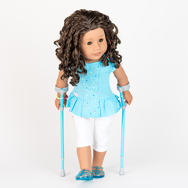 American Girl doll with curly brown hair, blue top, white trousers, and pale aqua crutches.