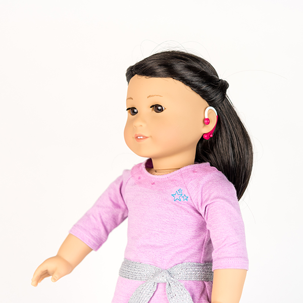 American Girl doll with brown hair, a pale pink dress and hot pink hearing aids.
