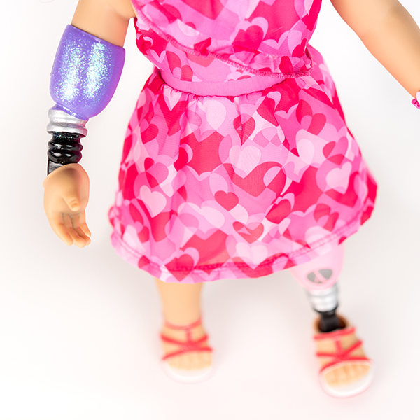 American Girl doll in pink and red dress with prosthetic leg and arm.
