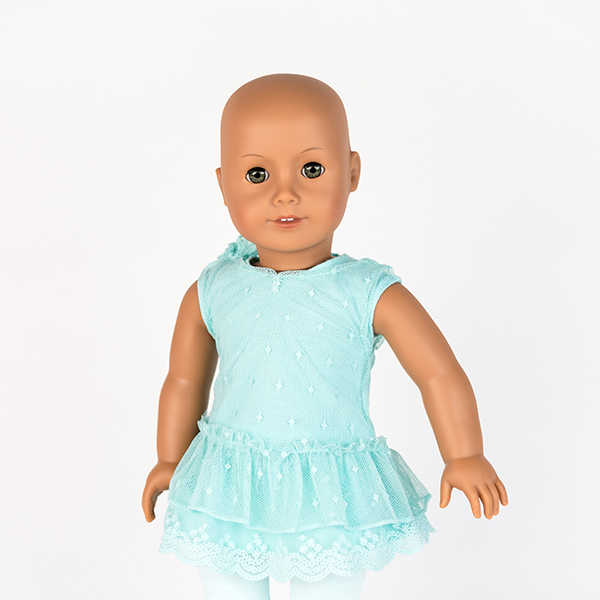 American Girl doll with no hair, blue eyes and blue lace dress.