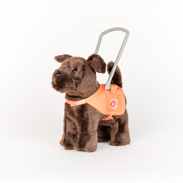 Image shows a plush guide dog. The dog is brown and has an orange and grey guide dog harness.
