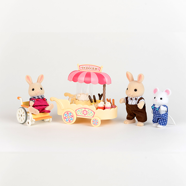 Image shows rabbit figure using a pink wheelchair working behind a popcorn wagon. There is another rabbit and a mouse waiting to be served.