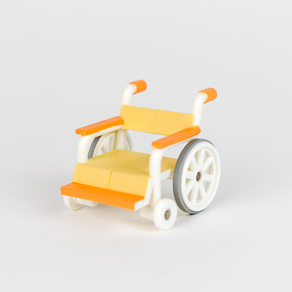 Image shows toy pink wheelchair.