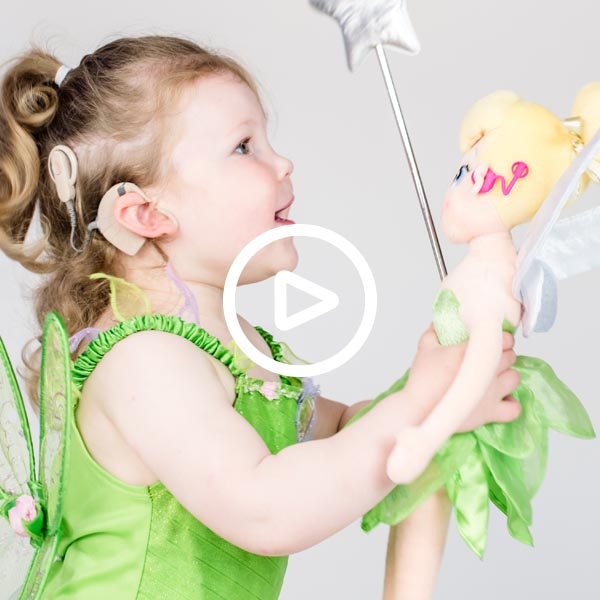 Smiling girl, aged two, with cochlear implant. The girl is dressed in a Tinkerbell outfit and is holding a silver wand and a plush Disney Tinkerbell doll with a hot pink cochlear implant.