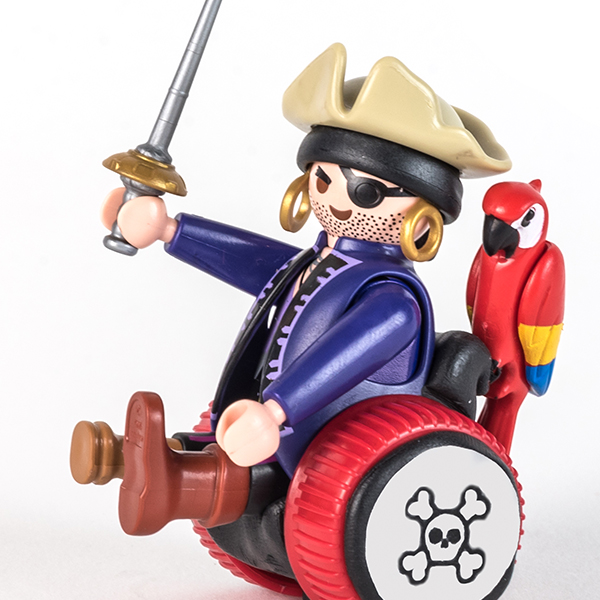 #ToyLikeMe makeover image of Playmobil pirage figure using a black and red wheelchair made of modelling clay.