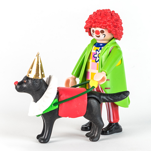 #ToyLikeMe makeover image of Playmobil clown figure with black guide dog. The dog is wearing a model clown