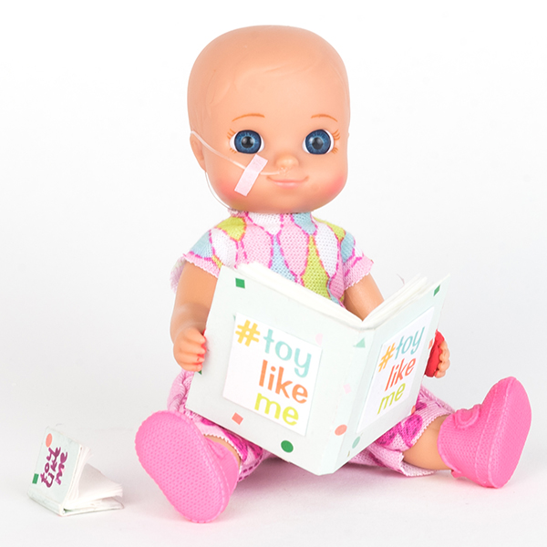 #ToyLikeMe makeover image showing baby girl toy with nasal feeding tube, reading a book.