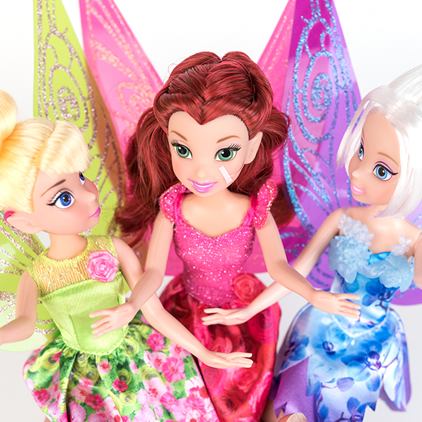 #ToyLikeMe makeover image showing Disney Tinkerbell and Periwinkle dolls with hot pink model cochlear implants chatting with Disney fairy Rosetta who has a nasal feeding tube.