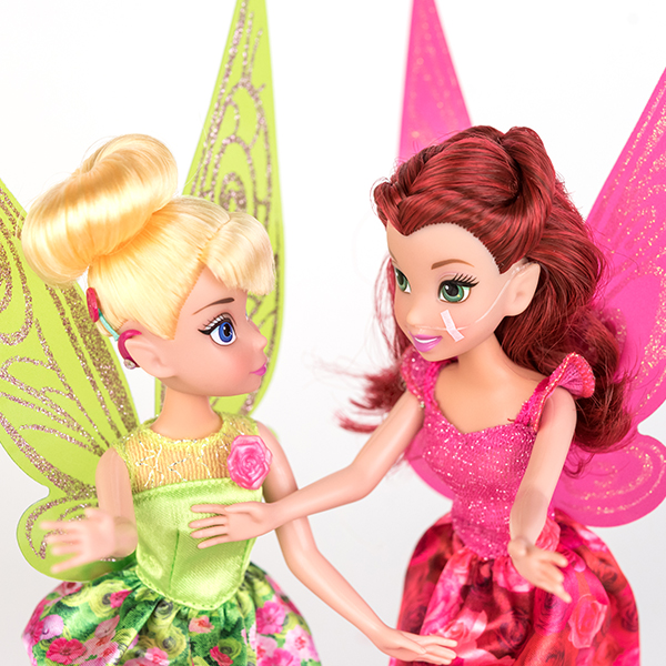 #ToyLikeMe makeover image showing Disney Tinkerbell doll with a hot pink model cochlear implant chatting with Disney fairy Rosetta who has a nasal feeding tube.