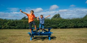 Two boys jumping off a picnic table.